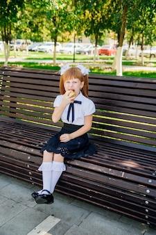 Powrót do szkoły. śliczna mała uczennica siedzi na ławce na dziedzińcu szkolnym i gryzie zielone jabłko.