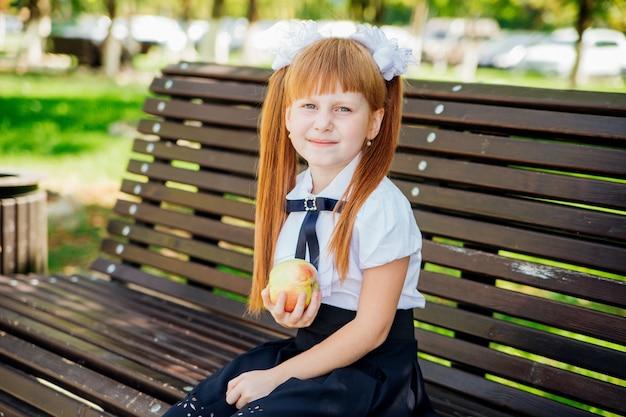 Powrót do szkoły. śliczna mała uczennica siedzi na ławce na szkolnym dziedzińcu i trzyma zielone jabłko.