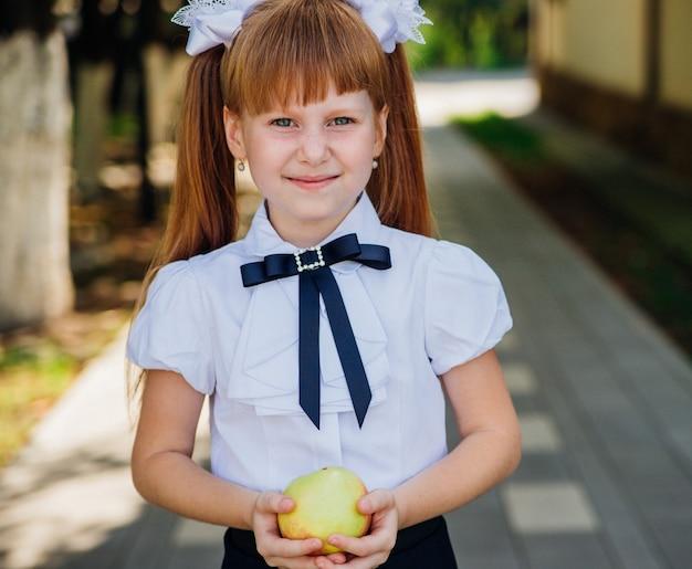 Powrót do szkoły. śliczna mała uczennica stoi w parku lub na szkolnym dziedzińcu i trzyma w rękach zielone jabłko. właściwe posiłki szkolne na lunch. mała dziewczynka idzie do pierwszej klasy.