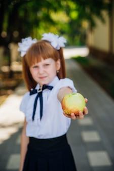 Powrót do szkoły. śliczna mała uczennica stoi w parku lub na szkolnym dziedzińcu i trzyma zielone jabłko.
