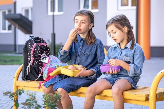 Powrót do szkoły. śliczne małe uczennice siedząc na ławce na dziedzińcu szkolnym i jedząc obiad na świeżym powietrzu.