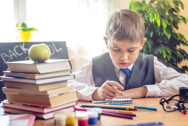 Powrót do szkoły. śliczny dziecka obsiadanie przy biurkiem w sala lekcyjnej. chłopiec uczy się lekcji