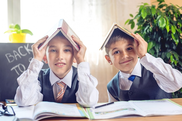 Powrót do szkoły. słodkie dzieci siedzą przy biurku w klasie.