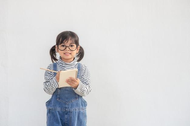 Powrót do szkoły. śmieszna dziewczynka w okularach na białym tle. dziecko ze szkoły podstawowej z książką.