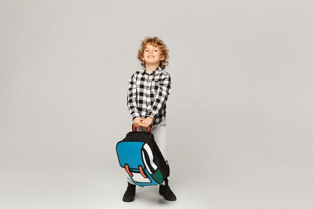 Powrót do szkoły. śmieszny chłopiec ze szkoły podstawowej pozuje z plecakiem, odizolowywającym