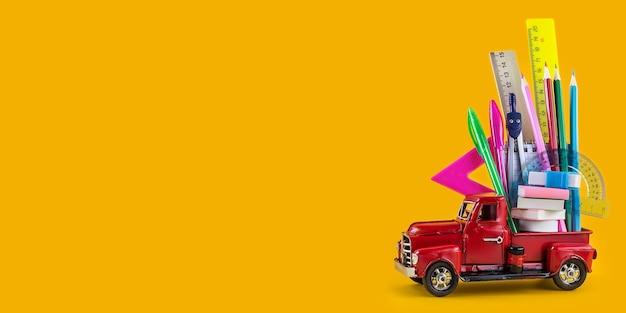 Powrót do szkoły sprzedaży tła. samochód dostarczający szkolne materiały piśmienne na żółtym tle. kompozycja z różnych papeterii szkolnej na kolor tła. koncepcja edukacji. długi, szeroki baner