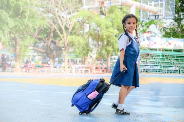 Powrót do szkoły. szczęśliwa uśmiechnięta dziewczyna od szkoły podstawowej przy szkolnym jardem.
