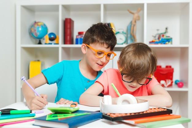 Powrót do szkoły. szczęśliwe dzieci siedząc przy biurku i odrabiania lekcji. uczeń szkoły podstawowej w klasie pisania i czytania. szkolnictwo domowe i edukacja w domu. chłopcy na lekcji w klasie.