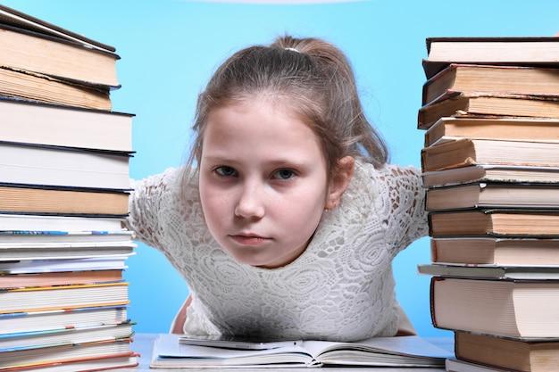 Powrót do szkoły. szczęśliwe słodkie pracowite dziecko siedzi przy biurku w pomieszczeniu. dzieciak uczy się w klasie, po bokach góry książek