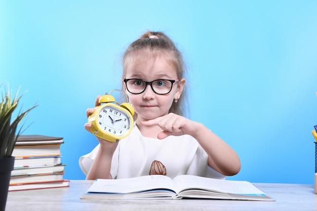 Powrót do szkoły. szczęśliwe słodkie pracowite dziecko siedzi przy biurku w pomieszczeniu. dziecko uczy się w klasie.