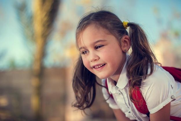Powrót do szkoły. szczęśliwy uczeń dziewczyna plenerowa. koncepcja dzieci i edukacji