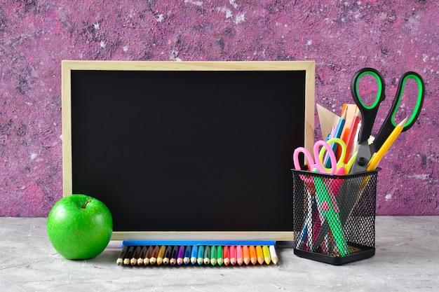 Powrót do szkoły. tablica szkolna, jabłko i papeteria na różowym tle znalazło miejsce na tekst. wakacje 1 września.