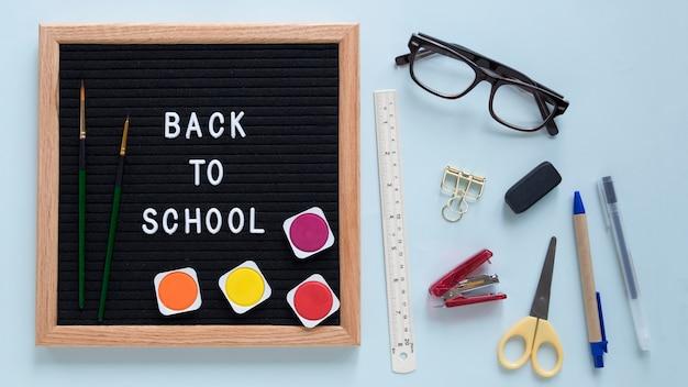 Powrót do szkoły tekst na tabliczce z kolorowe farby akwarelowe i pędzel w pobliżu różnych stationeries