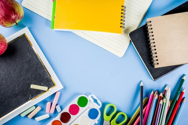 Powrót do szkoły tło z akcesoriami do sali szkolnej - farby, ołówki, zeszyty, książki, nożyczki, kreda, markery, niebieskie tło, powyżej miejsca na kopię