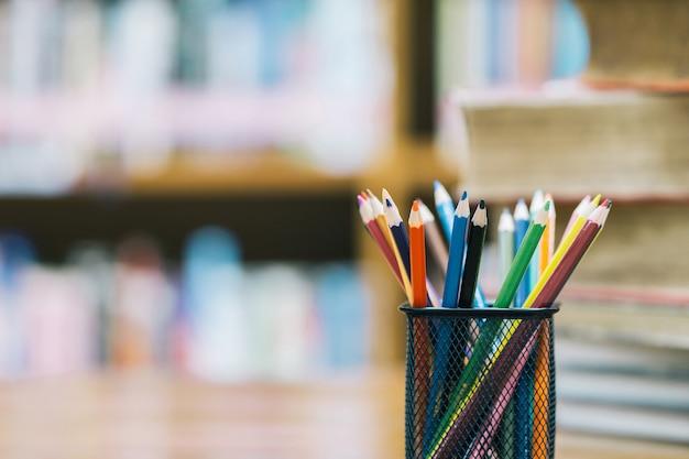 Powrót do szkoły tło z drewnianymi kolorowymi ołówkami w koszu do nieostrości. w klasie lub w bibliotece