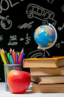 Powrót do szkoły tło z książek, ołówki i jabłko na białym stole.