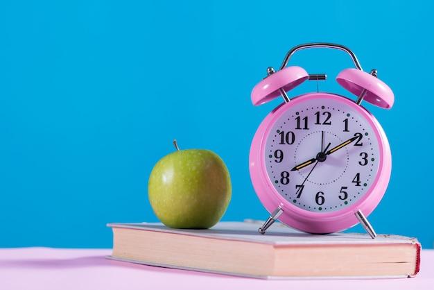 Powrót do szkoły tło z książkami, apple i budzikiem