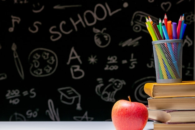 Powrót do szkoły tło z książkami, ołówkami i jabłkiem na białym stole.
