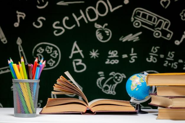 Powrót do szkoły tło z książkami, ołówkami i kulą ziemską na białym stole na zielonej tablicy