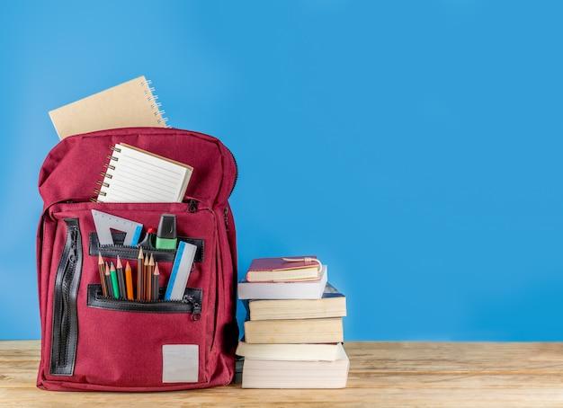 Powrót do szkoły . tornister i materiały na drewnianym stole z książkami