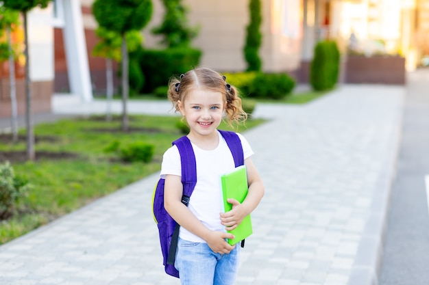 Powrót do szkoły, uczennica z plecakiem i książką w rękach idzie na naukę do pierwszej klasy