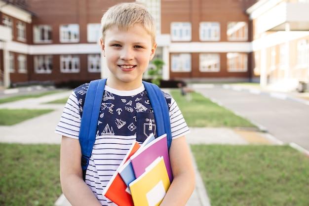 Powrót do szkoły. uśmiechnięty chłopiec ze szkoły podstawowej z notebookami i plecakiem. edukacja. dzień wiedzy.