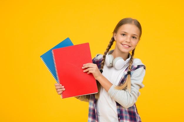 Powrót do szkoły. użyj notatnika lub książki. ucz się lekcji do egzaminu. znajdź inspirację w książce. cieszę się nauką. pewny swojej wiedzy. małe dziecko w zestawie słuchawkowym z notatnikiem. dziecko gotowe do nauki.