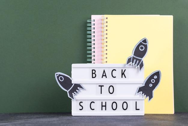 Powrót do szkoły w tle z zeszytami i podświetlanym pudełkiem