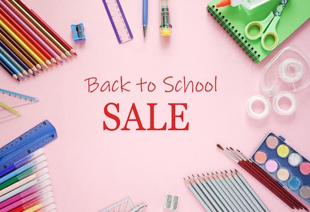 Powrót do szkoły wyprzedaż tekst i kredki, zeszyty, linijka, pisaki, na różowym tle. transparent