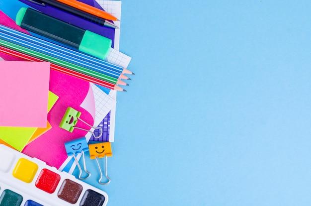 Powrót do szkoły z akcesoriami szkół - farby, ołówki, zeszyty, nożyczki, markery, niebieskie tło.