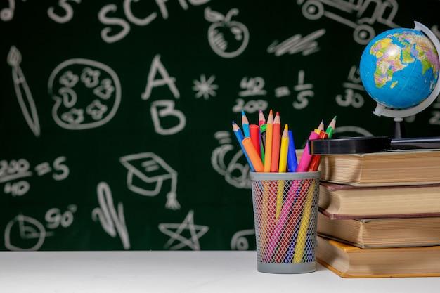 Powrót do szkoły z książkami, ołówkami i kulą ziemską na białym stole na zielonym tle tablicy.