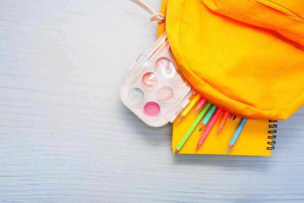 Powrót do szkoły z żółtym plecakiem i szkolnymi dostawcami na stole