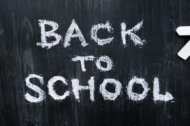 Powrót do szkoły zdanie napisane na czarnym tle drewna, widok z góry. nowy semestr, koncepcja edukacji: mieszkanie leżało odręcznie słowa i kawałki kredy na tablicy