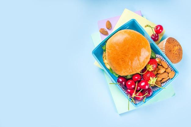 Powrót do szkoły, zdrowe smaczne pudełko na lunch dla dzieci z kanapkami, orzechami, świeżymi owocami i paluszkami warzywnymi