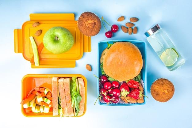 Powrót do szkoły, zdrowe smaczne pudełko na lunch dla dzieci z kanapkami, orzechami, świeżymi owocami i warzywami