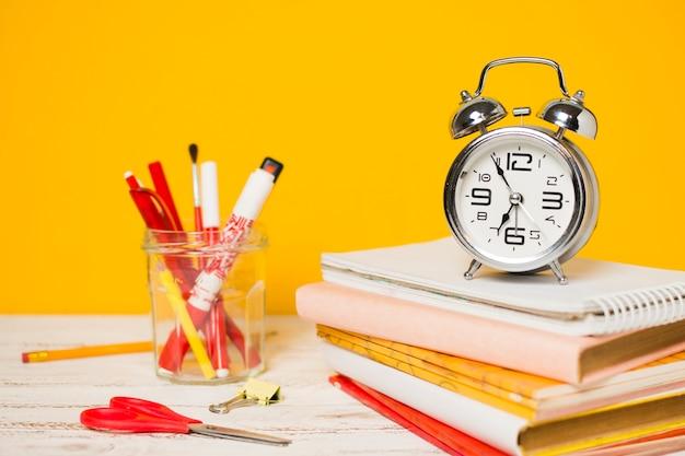 Powrót do szkoły zegar koncepcja na stosie książek