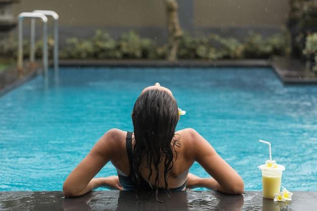Powrót kobiety w basenie z shake owocowy