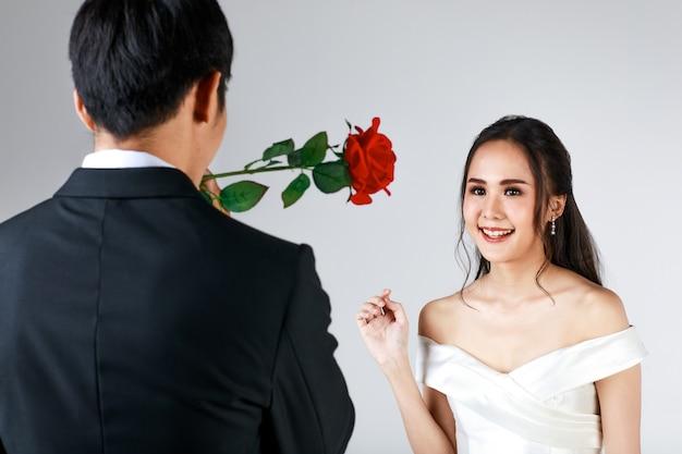 Powrót mężczyzny ubrany w czarny smoking dając róża do młodej atrakcyjnej kobiety azjatyckiej, wkrótce młodej pary, kobieta ubrana w białą suknię ślubną. koncepcja fotografii przedślubnej.