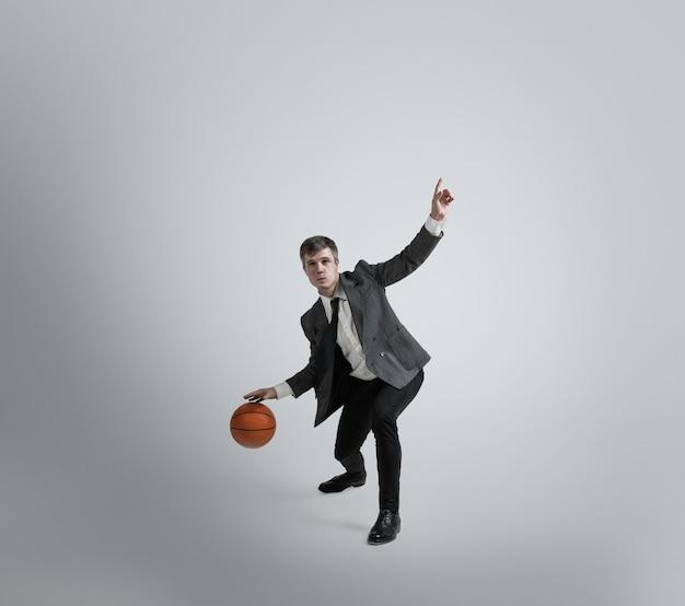 Powrót na studia – nigdy nie jest za późno na bycie gwiazdą sportu. człowiek w biurze ubrania trenuje w koszykówce na szarej ścianie. niezwykły wygląd biznesmena w ruchu, akcji. sport, zdrowy styl życia.