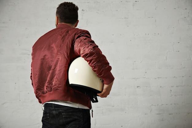 Powrót strzał mężczyzny w dżinsach, krótkiej kurtce z terakoty z błyszczącym białym kaskiem motocyklowym pod pachą na białym tle