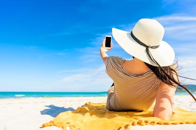 Powrót strzał modnej młodej kobiety nie do poznania w dużym białym kapeluszu leżącym na piasku tropikalnej plaży przy selfie ze smartfonem udostępnianie wakacji w sieci społecznościowej. jasne żywe kolorowe zdjęcie