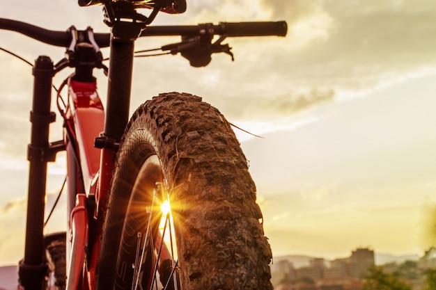Powrót strzał z roweru górskiego na zachód słońca. tylne koło. opona na rower górski. opony element rowerowy mtb 27,5 cala.