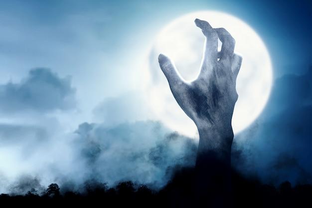 Powstanie ręki zombie w nocy z ziemi