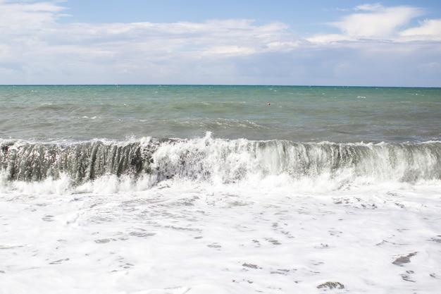 Powstawanie dużej fali burzowej nad wodą z pianą