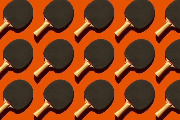 Powtarzające się czarne rakiety tenisowe do tenisa stołowego z twardym cieniem na pomarańczowym tle, sprzęt sportowy do tenisa stołowego