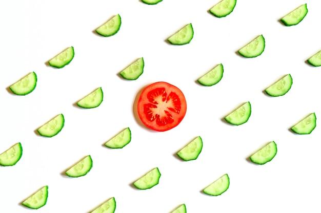 Powtarzający się wzór pokrojonych w plasterki półokręgów świeżych surowych ogórków warzywnych do sałatki i pomidora