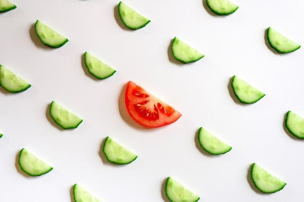 Powtarzający się wzór pokrojonych w plasterki półokręgów świeżych surowych ogórków warzywnych na sałatkę i plasterek pomidora w środku na białym tle na białym tle płaski świecki, widok z góry