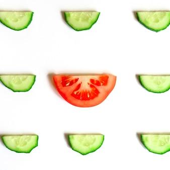 Powtarzający się wzór pokrojonych w plasterki półokręgów świeżych surowych ogórków warzywnych na sałatkę i plasterkiem pomidora w środku na białym tle na białym tle płaski świecki, widok z góry. kwadrat