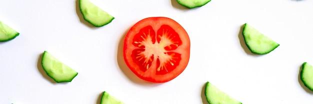 Powtarzający się wzór pokrojonych w plasterki półokręgów świeżych surowych ogórków warzywnych na sałatkę i plasterkiem pomidora w środku na białym tle na białym tle płaski świecki, widok z góry. transparent