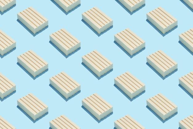 Powtarzalny wzór z kostek mydła na pastelowym niebieskim tle.